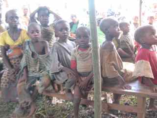 Pygmy children listening to preaching 4