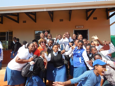 Shari Brink  and fellow-traveler Jordan Banks  celebrate with kids at Matamzama Dube High School where the Collegiate Churches have built three classrooms.