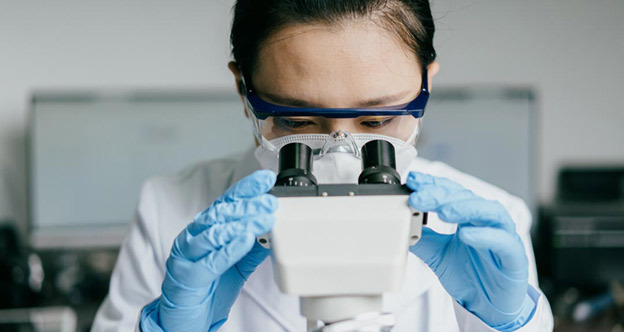 Researcher in a while lab coat, blue medical gloves and protective eye glasses looks into microscope